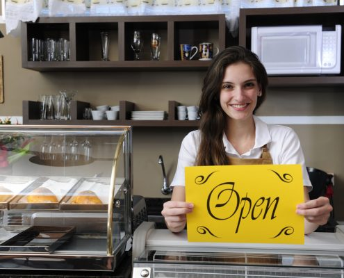Small business: Happy owner or waitress of a cafe showing open sign