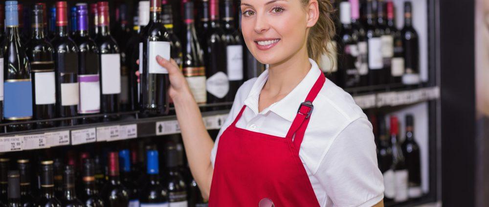 Portrait of a smiling blonde worker taking a wine bottle in supermarket
