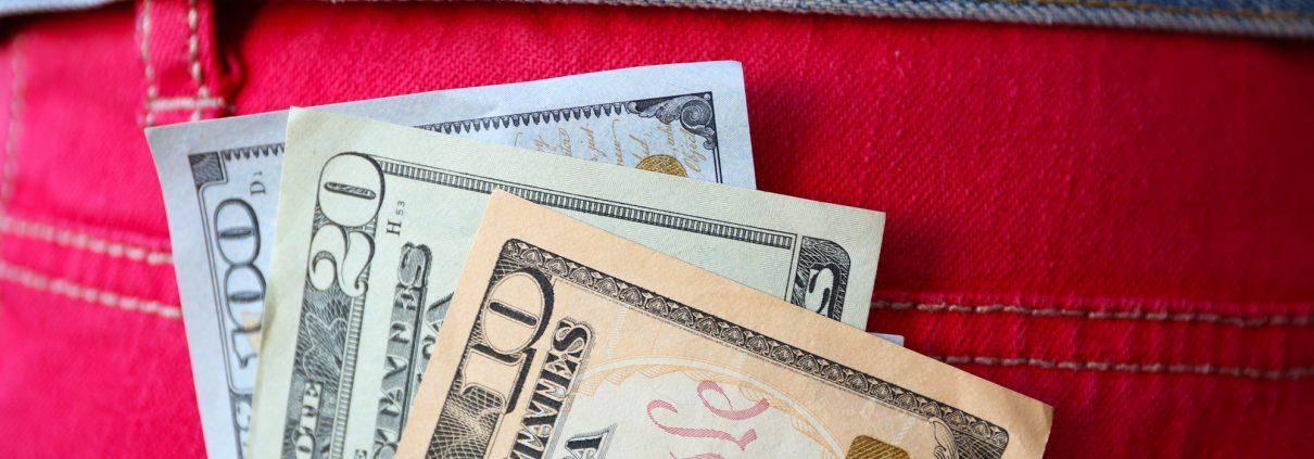 Dollar banknotes in jeans pocket closeup