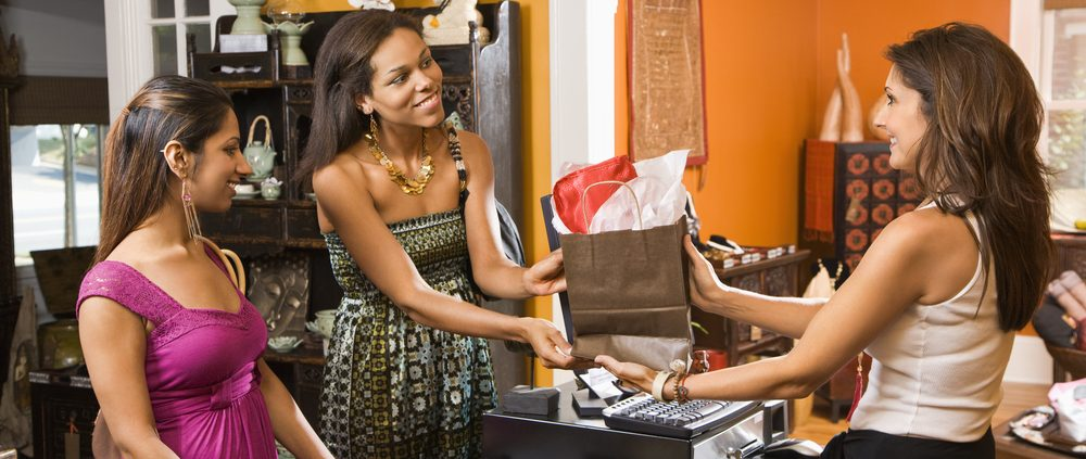 Two women making purchase  from sales clerk in boutique.