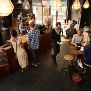 High angle view of a busy popular coffee shop with modern styling in which there are customers sitting and talking, a waiter serving coffee, and baristas helping other customers